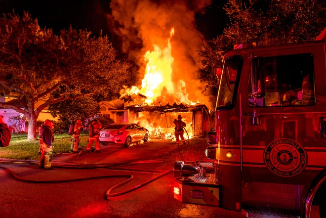 Fire consumes a Chets Creek Drive home Monday night, as well as a car parked outside, as firefighters battle it.