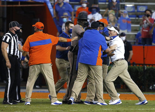 Florida coach Dan Mullen, right, seen here being held back by coaches and law enforcement after a fight broke out at the end of the first half against Missouri, faces the biggest game of his Gators' tenure Saturday against Georgia. He doesn't want to fall to 0-3 against UF's biggest rival.