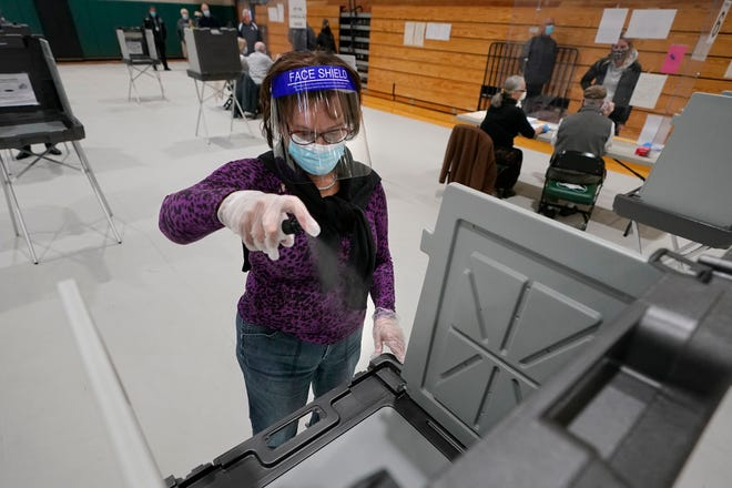 Poll worker Kathy Richardson uses a spray bottle to sanitize a voting booth out of concern for the coronavirus in a polling station at Marshfield High School on Tuesday in Marshfield, Mass.
