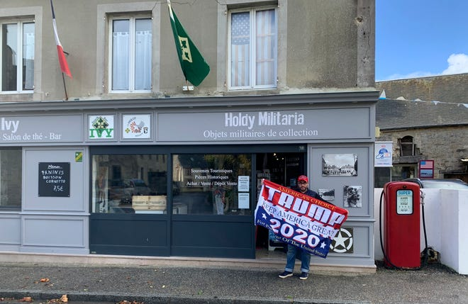 Philippe Tanne, of France, holds a Trump 2020 flag outside the military memorabilia store he runs in the Normandy town of Sainte-Marie-du-Mont, one of the sites of D-Day invasion in 1944, on Tuesday. Tanne, a French former soldier who hopes Trump wins reelection, is among the multitudes of people across the globe for whom the U.S. election is not a far-away happening in a far-away land but an impossible-to-ignore big deal for the planet. (Courtesy of Philippe Tanne via AP)