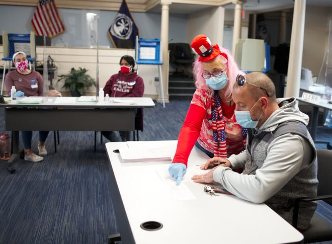 Volunteer Lois LaPietra-Kaplan helps Jason Brown update his voting information at Middletown Town Hall on Election Day 2020.