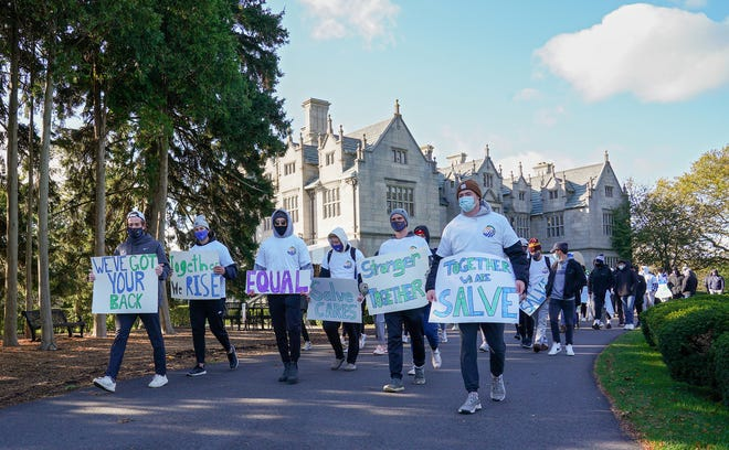 Salve Regina University students participate in an inclusion walk through campus on Monday. The event, organized by senior ice hockey player Paul Boutoussov, was held as part of the NCAA's Diversity and Inclusion campaign.