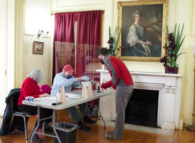 Polling volunteers help a voter register before casting his vote in Tuesday's election at the Edward King House.