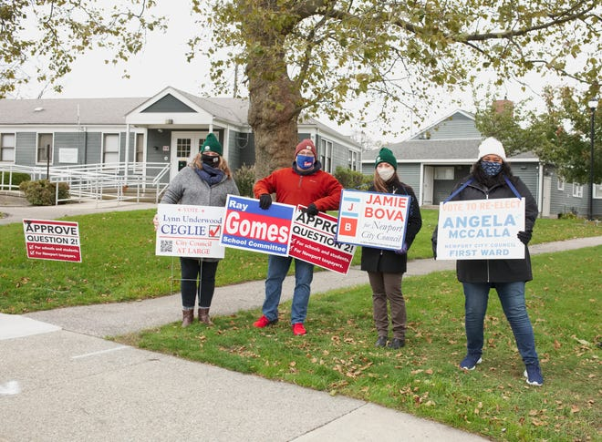 Masked candidates hold their signs outside the Park Holm polling place on Tuesday morning.