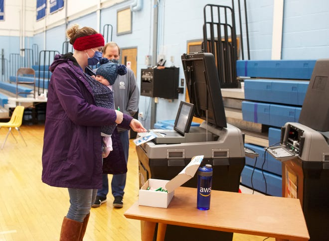 Katie Ciulla holds her daughter Anna Joy as she casts her ballot on Election Day at Middletown High School on Tuesday.