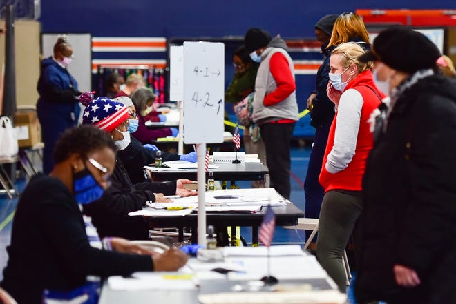 People prepare to vote on Election Day at the Parkway Center on Tuesday, Nov. 3, 2020 in Utica.