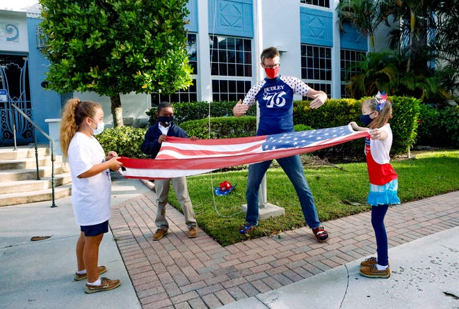Palm Beach Day Academy Head of School Fanning Hearon offers guidance as students, from left, Peyton Norton, Janson Bond, and Mandy Ellis fold the American flag on Nov. 3.