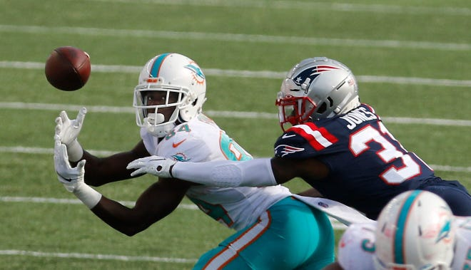 Wide receiver Isaiah Ford looks to haul in a pass as the Patriots' Jonathan Jones defends during this year's season opener on Sept. 13 at Gillette Stadium. The Patriots acquired Ford from the Dolphins before Tuesday's NFL trade deadline.