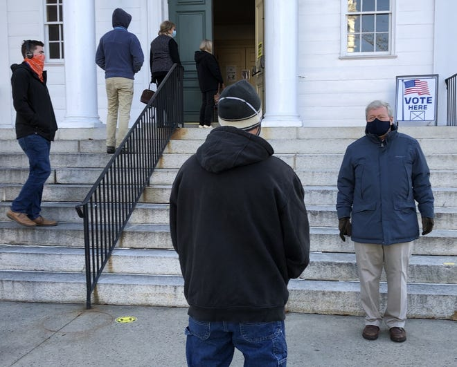 Incumbent State Rep. Christopher Babbidge, right, the Democratic candidate for Maine House District 8, greets voters as they line up outside Kennebunk Town Hall to vote on Tuesday, Nov. 3.