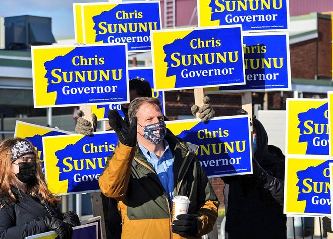 Gov. Chris Sununu, who won a third term Tuesday, stops at the Hampton polls to campaign with supporters on Election Day.