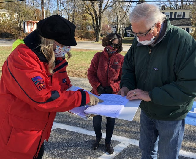 Volunteer Jennifer Comeau, left, checks in with a couple of voters as they arrive at the North Street Fire Station to vote in Kennebunkport on Tuesday, Nov. 3.