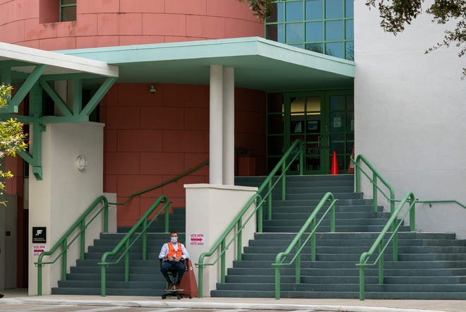 A poll worker waits for voters to arrive to cast their ballots at Eissey Campus Theater on election day in Palm Beach Gardens, Florida on November 3, 2020.