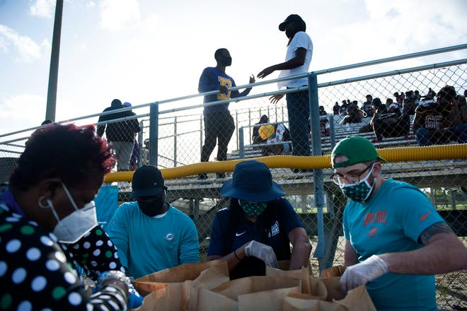 Junior Dolphins, part of The Miami Dolphins Youth Programs, and Baptist Health South Florida distributed meals, football equipment and other items to student-athletes at Boynton Beach High School on Monday.
