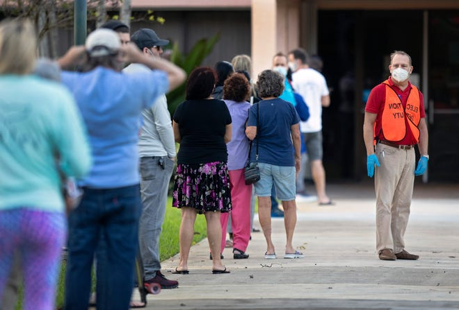Voters line up outside the Howard Park Community Center in West Palm Beach shortly before the polls opened at 7 a.m. Tuesday, Nov. 3, 2020.