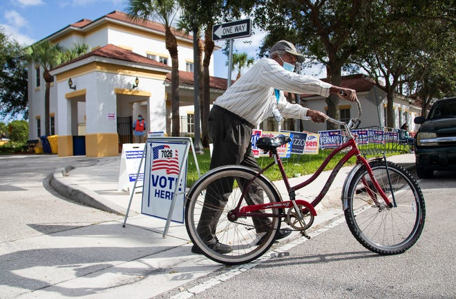 Claude Tolbert wheels his bicycle away after voting at the Lindsey Davis Senior Community Center in Riviera Beach Tuesday, Nov. 3, 2020.