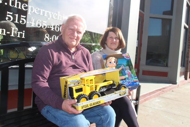 John and Linda Andorf hold a few of the toys purchased for the annual toy drive program. Collection boxes will be available at Perry business through Dec. 4.