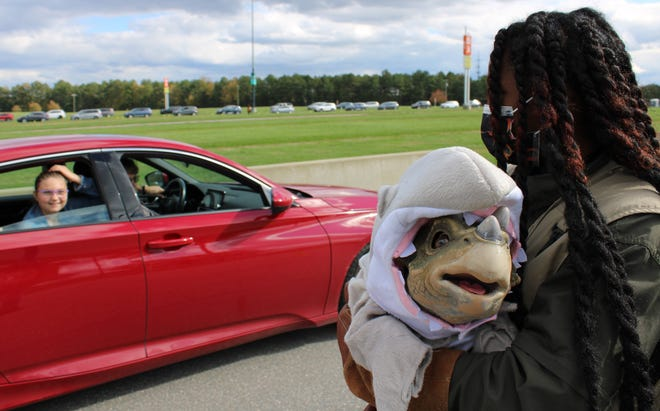 A Jurassic Quest dinosaur trainer introduces a baby dinosaur to drive-thru safari attendees at the Richmond Raceway in Richmond on October 31, 2020.