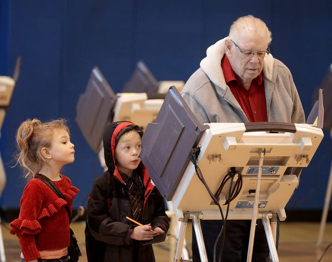 Wyane Maddy casts his vote at the Massillon Boys and Girls Club while his grandaughter Abigail Parsons,5, looks on and grandson Levi Parsons ,8, takes notes.
