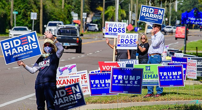 Supporters of candidates stand in front of the polling station in the Elks Lodge in St. Augustine on Tuesday.