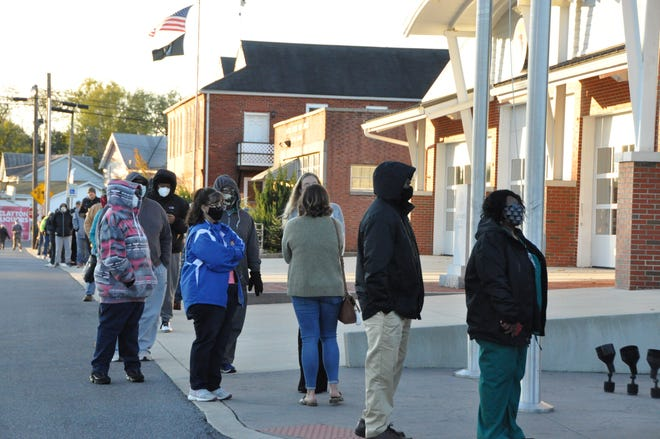 Voters wait in line outside the Clayton Firehouse at about 7:05 a.m., just after the polls opened this morning, with the line stretching from East Street along Railroad Avenue to Main Street.
