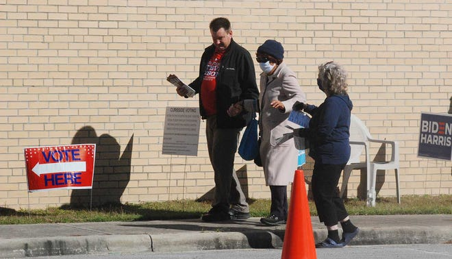 Republican campaign workers help an older black woman maneuver toward the voting site at Grover C. Fields School on Election Day.