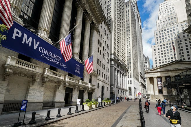Pedestrians pass the New York Stock Exchange Oct. 2 in New York. Stocks powered higher Tuesday after a bruising U.S. presidential campaign that sent markets spinning because of the uncertainty it sowed finally reached its end.