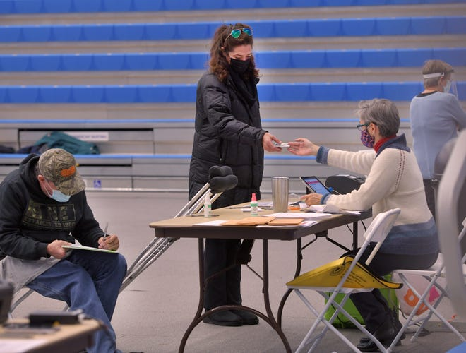 A woman is handed back her license at the Worcester State University polling site on Tuesday.