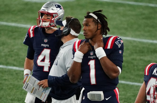 Patriots quarterback Cam Newton, right, looks on as offensive coordinator Josh McDaniels talks with quarterback Jarrett Stidham (4) on the sideline during the second half of New England's home game against the 49ers.