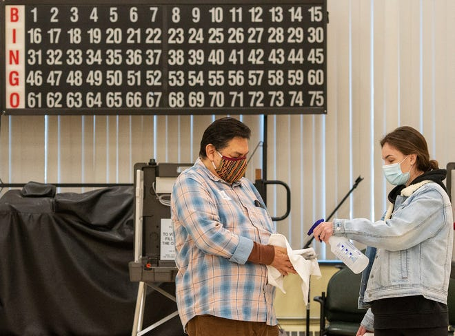 WORCESTER - Election volunteers Robert Ochoa and Julie McDermott sanitize pens used by voters at the Worcester Senior Center polling place Tuesday, November 3, 2020.