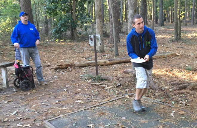 Justin Farrow, right, prepares to throw a disc on the B. Cordell Disc Golf Course at Arnette Park while Robert Herzog watches. [Steve DeVane/The Fayetteville Observer]