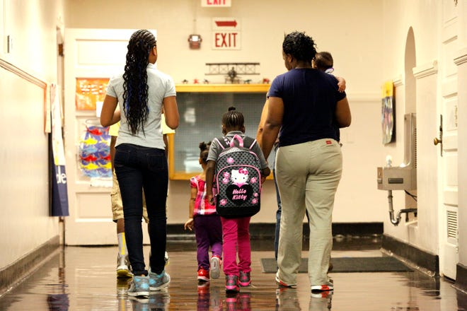 Family members walks with children on their first day of school in 2013.