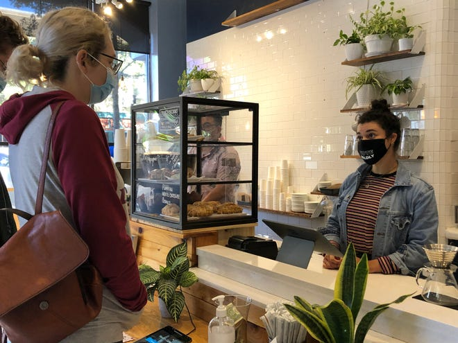 Wyatt's Coffee Barista Brittnee Greene takes a customer's order in November. Employees at retail spaces and patrons have been required to wear masks inside public facilities since county commissioners passed a mask mandate May 4, 2020.
