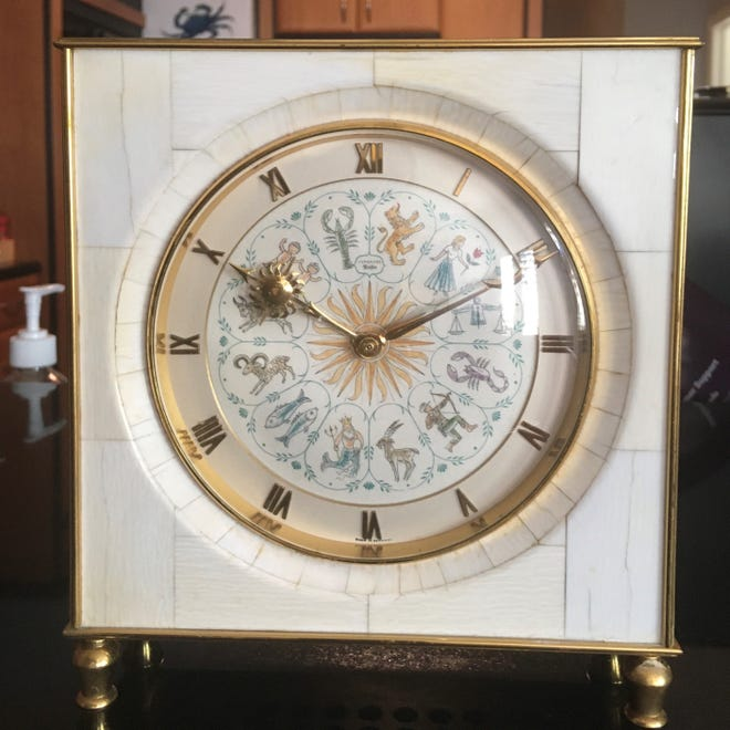 This Junghans clock includes elephant ivory and a zodiac-decorated dial.