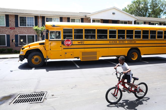 A child rides his bike past an Alachua County Public Schools bus equipped with Wi-Fi, parked at Gardenia Gardens Apartments in northeast Gainesville on April 20.