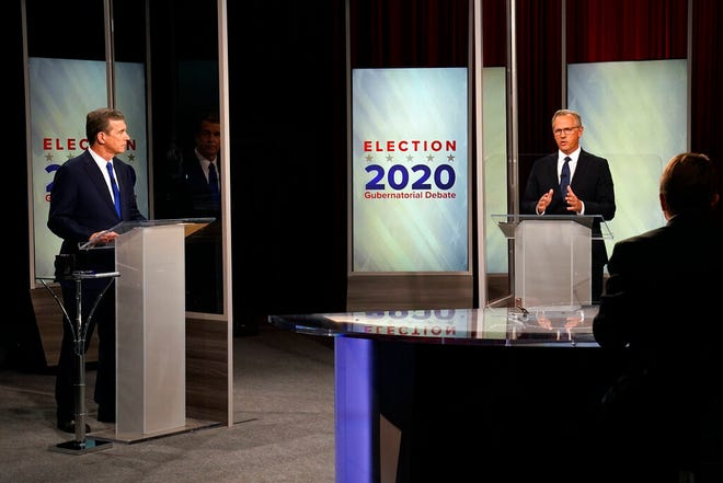 FILE - This Oct. 14, 2020, file photo shows North Carolina Gov. Roy Cooper, left, and Lt. Gov. Dan Forest during a live televised debate moderated by Wes Goforth at UNC-TV studios in Research Triangle Park, N.C. (AP Photo/Gerry Broome, File)