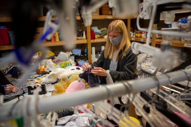 Volunteer Lisa Allender of Lewis Center sorts through donated clothing in the back room at the Common Ground Free Store Ministries in Delaware, on Oct. 27.