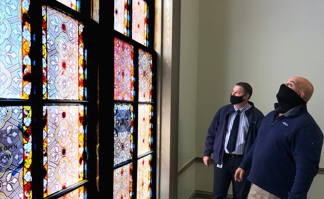Delaware County administrator Michael Frommer (left) and county facilities director Jon Melvin look at a painted window, which is nearly 15 feet tall, in the Delaware County Historic Courthouse on North Sandusky Street in Delaware. Removal of an added third floor now exposes the window's full length to those inside the building, which was constructed in 1869.