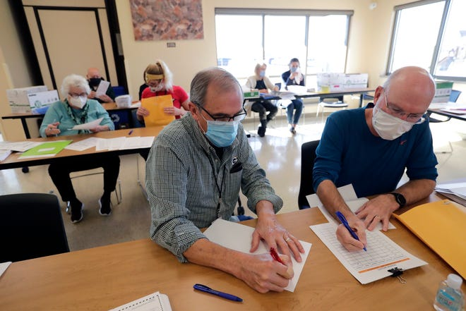 Tom Nudelbacher, left, and Jim Zipple are part of the team that's redoing ballots that had a printer error Tuesday, Nov. 3, 2020, at the Town Center Park in Grand Chute, Wis.