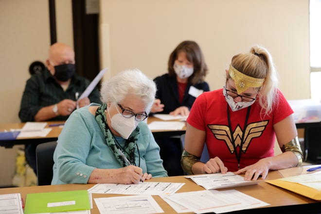 Jackie Lemberger, left, and Maureen Armstrong redo ballots that had a printer error Tuesday at the Town Center Park in Grand Chute.