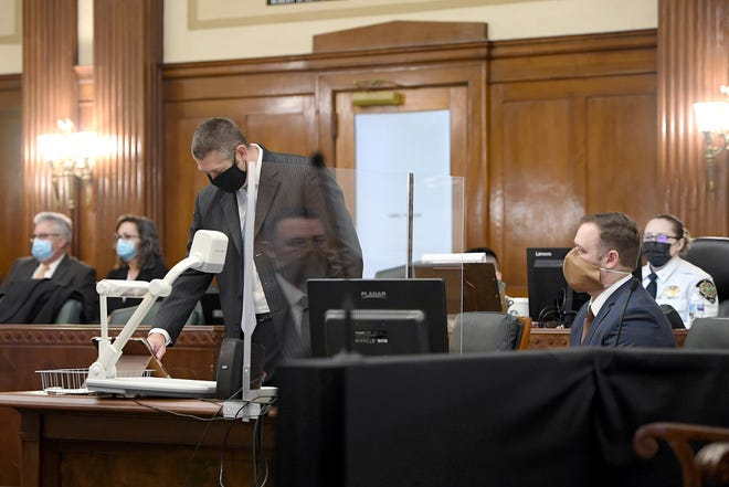 Former Asheville police officer Christopher Hickman is reflected in the divider placed between him and his attorney, Thomas Amburgey, as his final probation hearing in the 2017 beating of pedestrian Johnnie Rush at the Buncombe County Courthouse on Nov. 3, 2020. Hickman's charges were dismissed after the hearing.