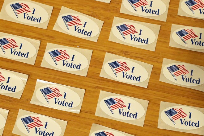 """FILE — """"I Voted"""" stickers are spread out on a table next to the ballot drop box for in-person voting at the Marvin Williams Recreation Center in Bremerton in November 2020."""