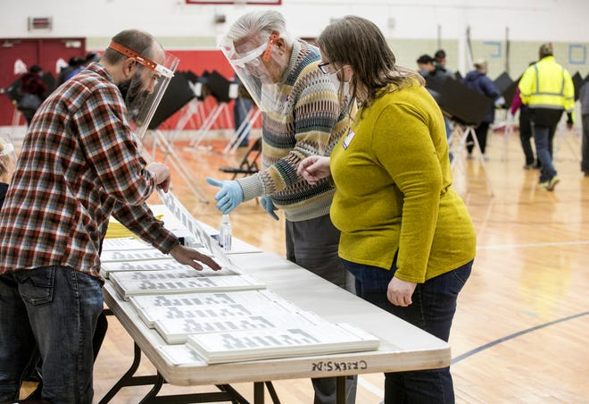 Poll workers take a provisional ballot at Creekside Elementary in Fairfield, Ohio, on Election Day, Tuesday, Nov. 3, 2020. Polls opened at 6:30 am and people were lined up before 6 am to cast their vote in this year's presidential election.