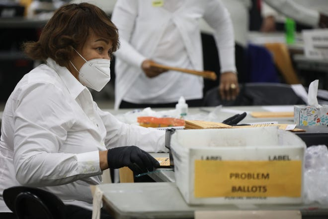 Poll workers count absentee ballots at the TCF Center Tuesday, Nov. 3, 2020 in Detroit.