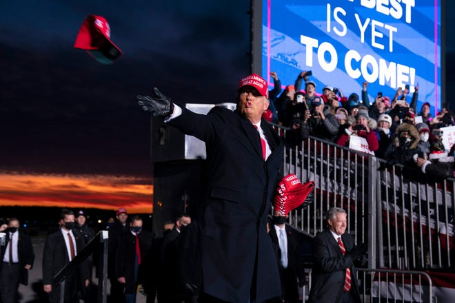 President Donald Trump throws hats to supporters as he arrives for a campaign rally at Cherry Capital Airport, Monday, Nov. 2, 2020, in Traverse City, Mich. (AP Photo/Evan Vucci)