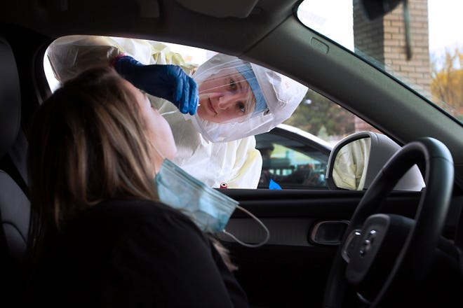 Lauren Bomke, an EMT with UCHealth, tests a person for COVID-19 at the UCHealth Laboratory – Harmony Campus drive-thru testing site recently. Drive-thru testing sites are experiencing the COVID-19 surge with more consistent traffic.