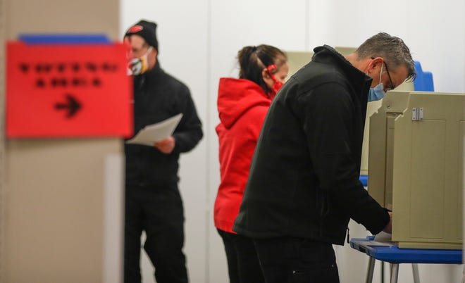 Tom Nordwig, left, Laura Krause and Mark Vanderleest cast their votes on Election Day at the old Sears building located in the Green Bay Plaza.