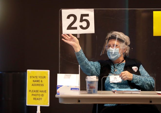 An election inspector waves to the next person in line at the Johnsonville Tailgate Village presidential polling location on the Lambeau Field property on Nov. 3, 2020, in Green Bay, Wis.