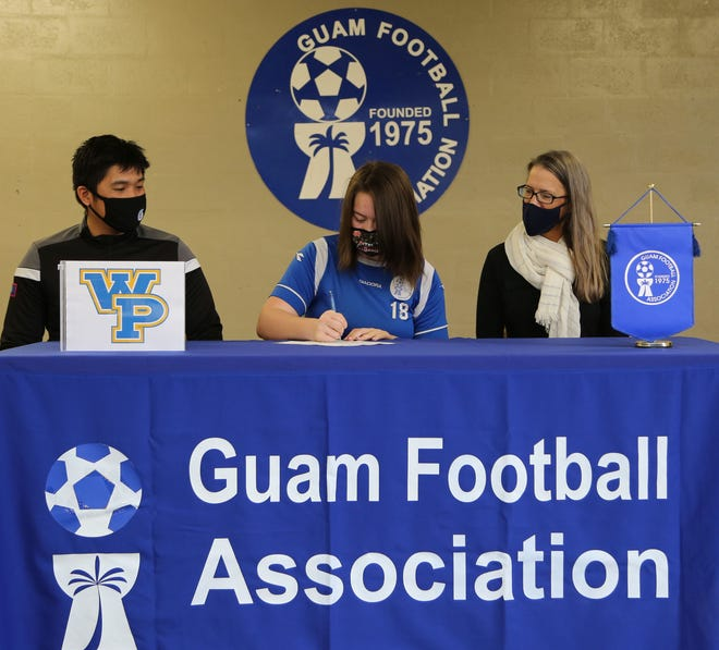 Guam women's national program athlete and Tiyan High School senior Rylee Guzman, center in blue, signs an early letter of intent to play intercollegiate women's soccer for the William Penn University Statesmen during a recent college signing event at the Guam Football Association National Training Center. Guzman also accepted a scholarship offered to her during the recruiting process.