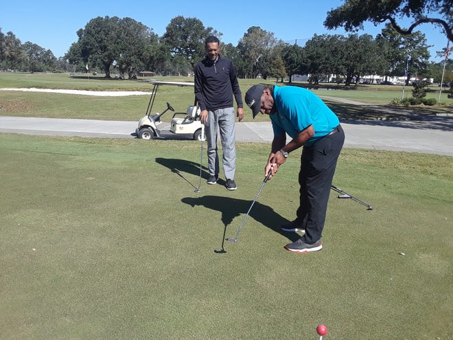 Chris Arceneaux, newly named head golf professional at Hebert Municipal Golf Course, shares some putting techniques with Darrell Boudreaux on the Hebert practice green.