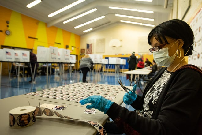 """Election worker Erica Bates of Lansing cuts up """"I Voted"""" stickers on Tuesday, Nov. 3, 2020, at Willow School in Lansing, Mich. [AP Photo/Matthew Dae Smith via Lansing State Journal]"""